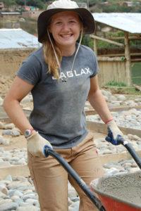 Woman with a wheelbarrow on a BSPC mission trip