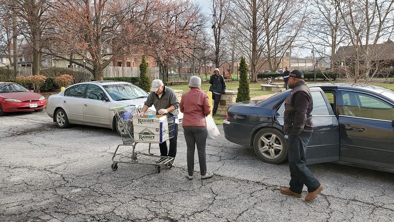 Food Pantry Volunteers Delivering Food to Shoppers' Cars in Food Pantry Driveway